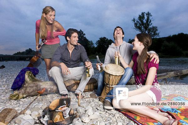 Gruppe von Freunden genießen Bier und Würste auf Party am Flussufer im Sommer