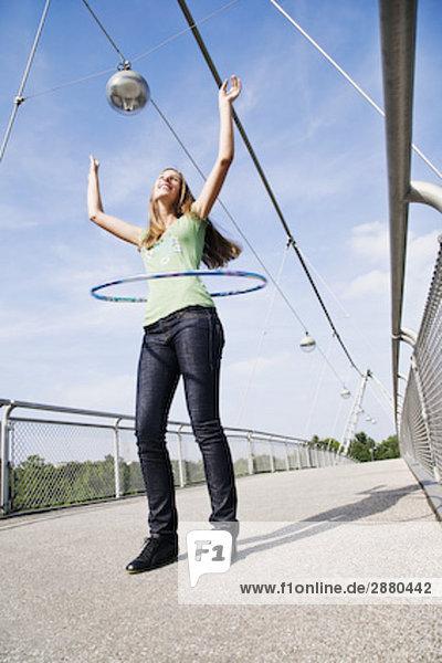 Young Frau macht Hula Hoop auf Brücke