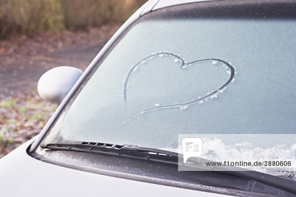 still life of heart drawn in frost on car window