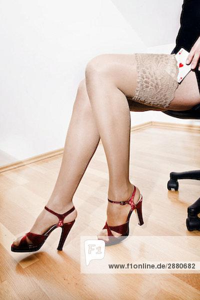 Detail der junge Frau Glücksspiel putting Herz-Ass in ihrem Nylon-Strümpfe