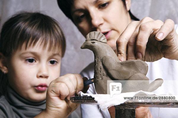 Mutter und Tochter bilden Skulptur von Clay zusammen
