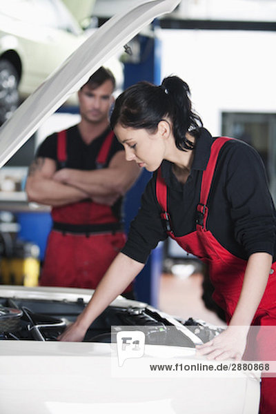 portrait of female mechanic repairing car with male colleague watching