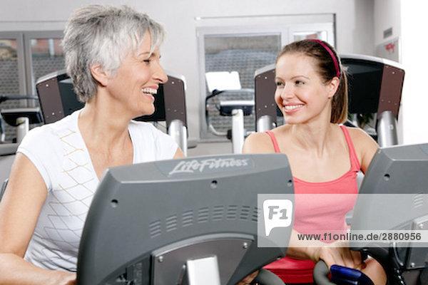 zwei Frauen auf Standfahrrädern im Fitness-Studio an jedem anderen lächelnd