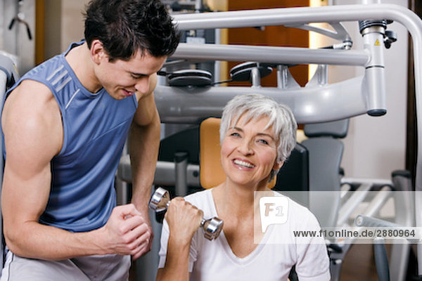 junger Mann zeigt reife Frau  wie Sie mit dumb Bell ausüben