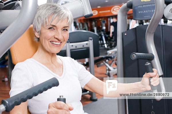 mature Frau beim training auf Gewicht Maschine im Fitness-Studio