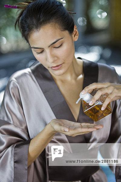 Frau gießt Öl aus einem Spender auf die Hand