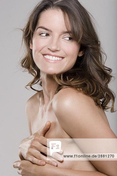 Nahaufnahme einer Frau  die ihre Brust bedeckt und lächelt