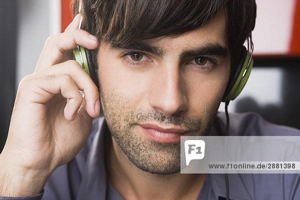 Porträt eines Mannes  der Kopfhörer hört