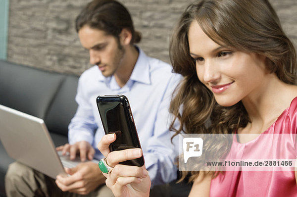 Frau liest Textnachricht auf einem Mobiltelefon
