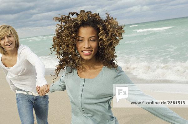 Girl holding hand of a teenage boy on the beach