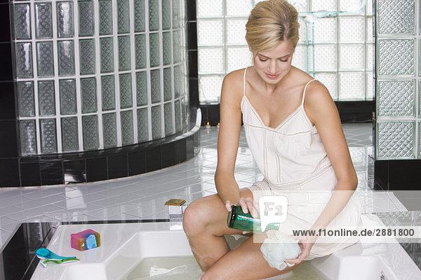 Frau gießt flüssige Seife auf einen Luffa