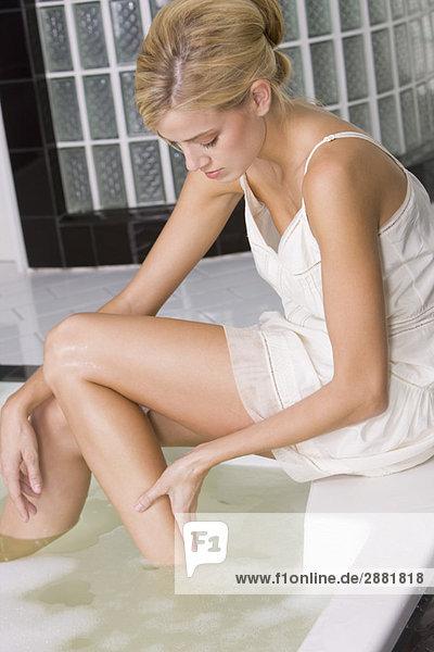 Frau wäscht sich die Beine in der Badewanne.