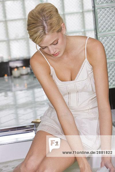 Frau am Rand einer Badewanne sitzend