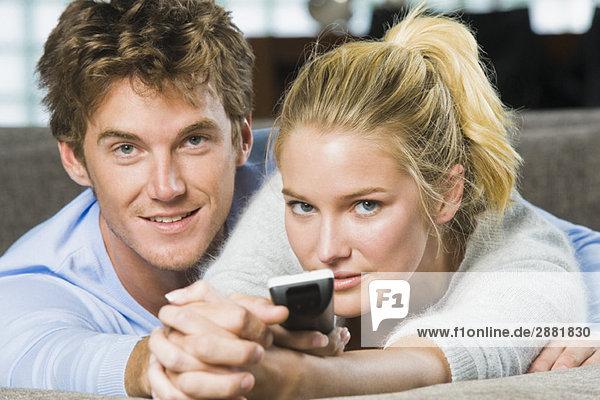 Porträt eines Paares mit Fernbedienung und Lächeln
