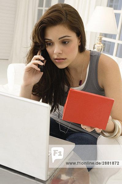 Frau online einkaufen und mit dem Handy telefonieren