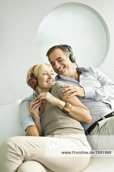 Paar Musik hören mit Kopfhörer und Lächeln