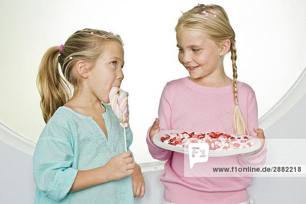 Mädchen hält einen Teller mit Geleebohnen  während ihre Freundin neben ihr einen Lolli isst.