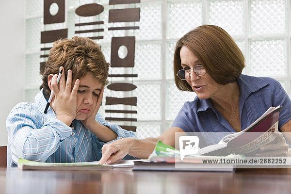 Frau hilft ihrem Enkel bei den Hausaufgaben