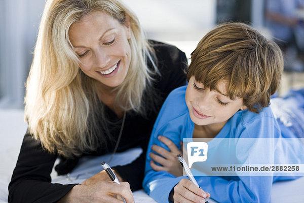 Frau hilft ihrem Sohn bei den Hausaufgaben