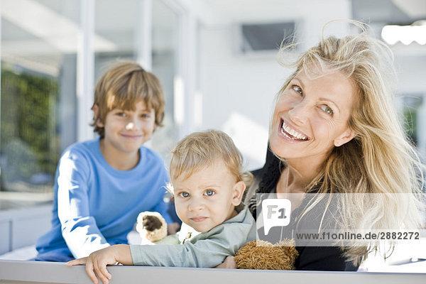 Porträt einer Frau  die mit ihren beiden Söhnen lächelt