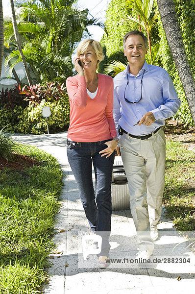 Mann zieht sein Gepäck neben einer Frau  die auf einem Handy spricht