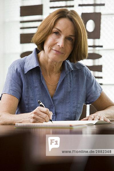 Porträt einer Frau  die in ein Notizbuch schreibt