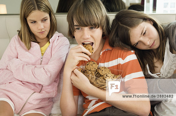 Boy eating chocolate cookies with two girls beside him