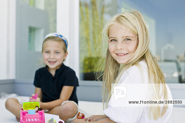 Portrait of two girls playing with toys