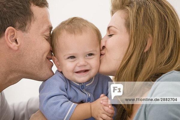 Eltern  die ihre Tochter küssen