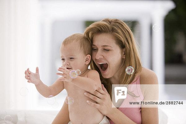 Kleines Mädchen fängt Blasen mit ihrer Mutter