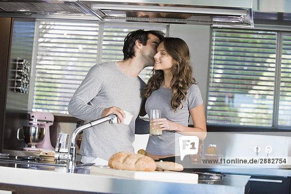 Mann küsst eine Frau in der Küche