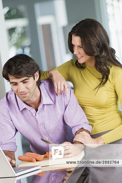 Mann kocht mit dem Rezept auf einem Laptop und eine Frau steht neben ihm.