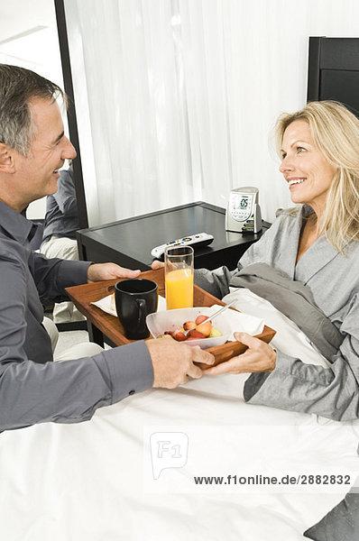 Mann gibt seiner kranken Frau Erfrischung