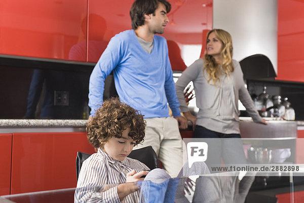 Junge spielt ein Videospiel mit seinen Eltern im Hintergrund