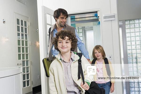 Mann mit seinen Kindern beim Betreten eines Hauses