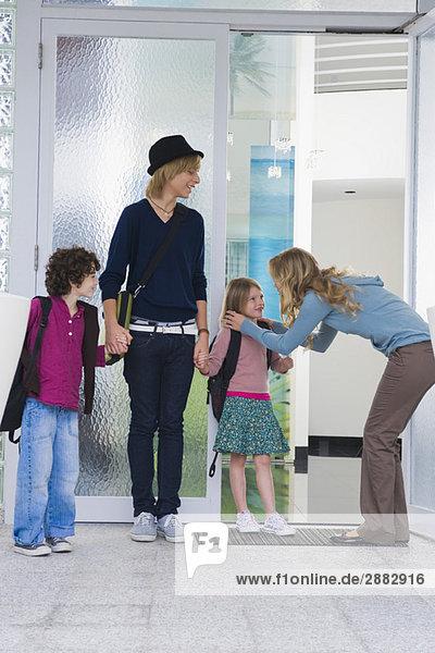 Frau mit ihren Kindern und einem Kindermädchen am Eingang eines Hauses