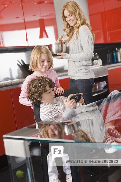 Junge spielt ein Videospiel mit seiner Schwester und Mutter im Hintergrund