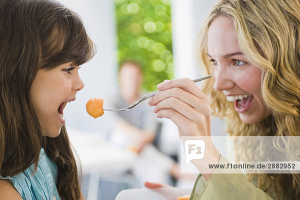 Woman feeding fruit salad to her daughter