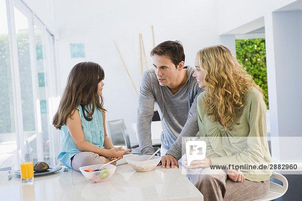 Mädchen mit ihren Eltern am Frühstückstisch