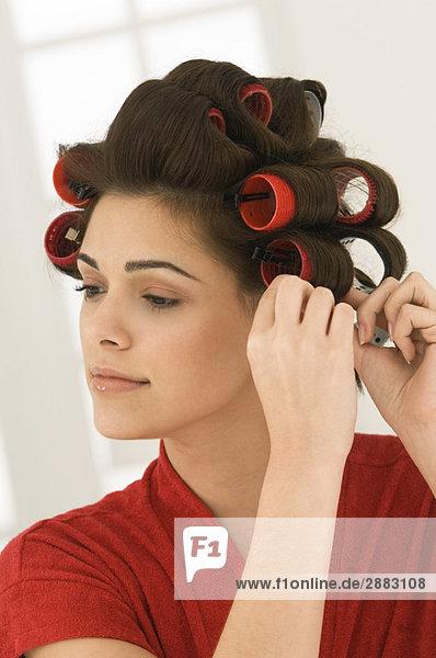 Woman adjusting curlers in her hair