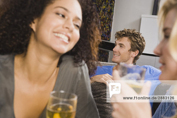 Drei Freunde genießen Getränke auf einer Party