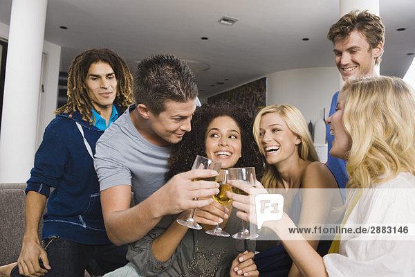 Freunde toasten mit Weingläsern auf einer Party