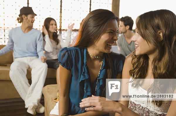 Zwei Frauen lächeln mit ihren Freunden im Hintergrund