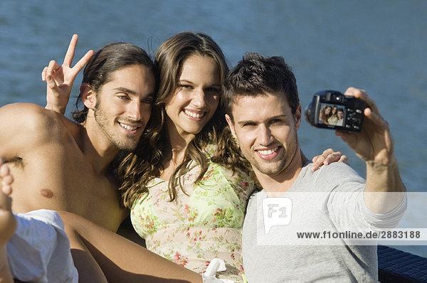 Drei Freunde  die mit einer Digitalkamera ein Foto von sich machen