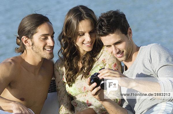 Drei Freunde beim Betrachten einer Digitalkamera