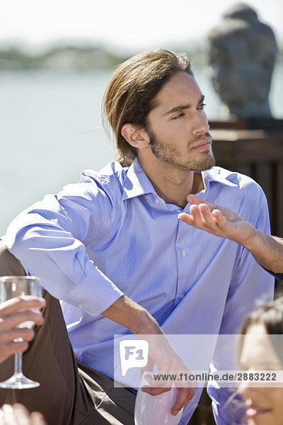 Mann genießt Getränke mit seinem Freund auf einer Party