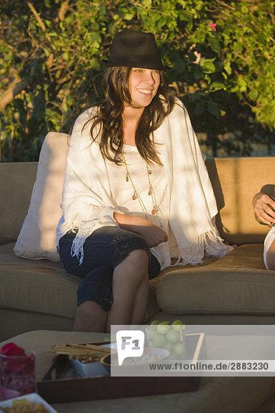 Frau auf der Couch sitzend und lächelnd