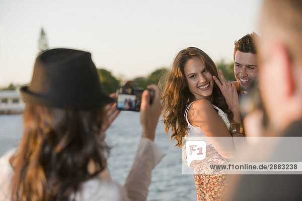 Frau beim Fotografieren ihrer Freunde mit der Kamera