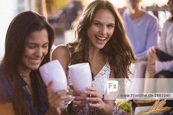 Zwei Frauen  die mit ihren Freunden im Hintergrund trinken.