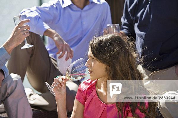 Frau genießt Drinks mit ihren Freunden auf einer Party